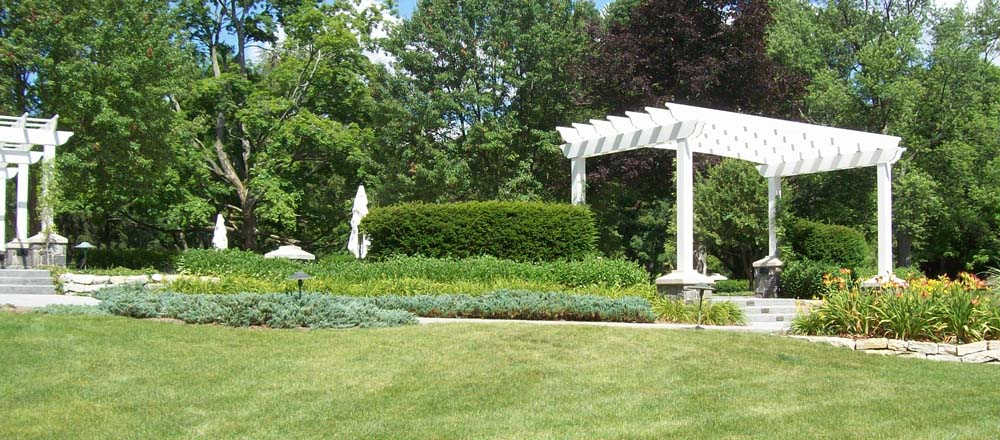 White gazebo surrounded by green grass and bushes.