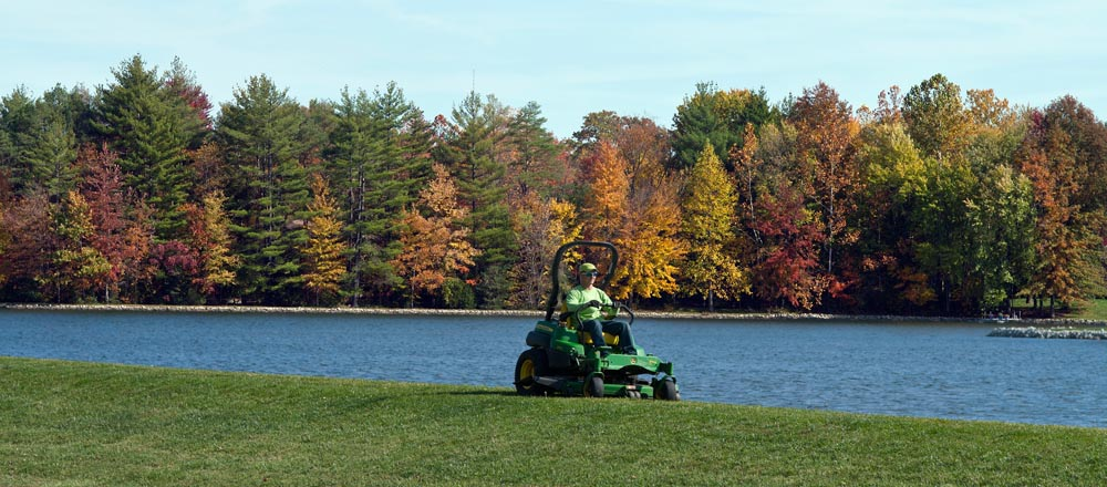 Engledow employee mowing lawn in front of lake.