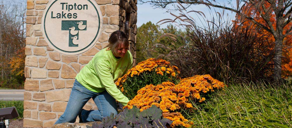 Engledow employee planting flowers outside neighborhood entrance.