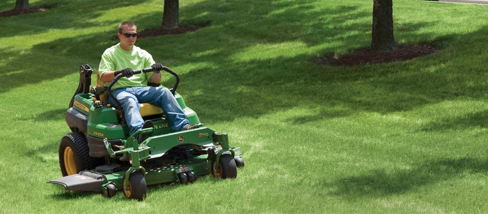 Engledow employee mowing grass.