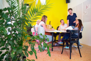 Designers, sitting in at a large table in a creative environment and office, surrounded by tack boards with drawings, plants and a bright yellow wall