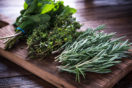 Rosemary, thyme, and mint from a garden laying on cutting board