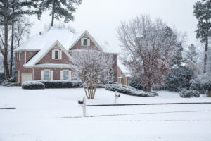 Brick house and landscape covered in snow