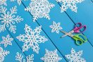 Multiple cutout snowflakes laying flat on a blue wooden table with a pair of scissors